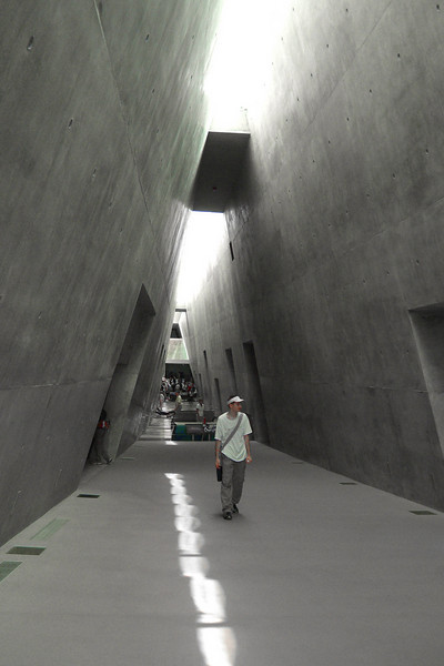 5-Spine of the main hall of the Holocaust History Museum: looking back (SE) and downward from the exit, toward the entry. The walls are reinforced concrete. The skylight protrudes through the mountaintop.