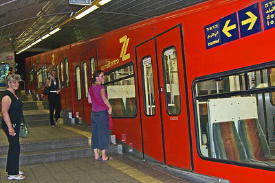 "25-Boarding the Carmelit (""Kar-mel-eet"") at Paris Square, the lower terminus. The Carmelit is an underground funicular. Since the gradient varies along the route, the floor of each car is never quite level, and slopes slightly ""uphill"" or ""downhill"" depending on the location."