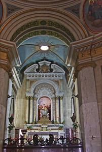 """11-Stella Maris interior. At bottom of this photo is the front of a platform that is built above an open cave (not shown) in which the prophet Elijah is believed to have lived and taught (9th century BCE). On the platform is a stone altar (shown here) and a statue of the Virgin Mary carrying Jesus on her knees—""""Our mistress of Carmel."""""""