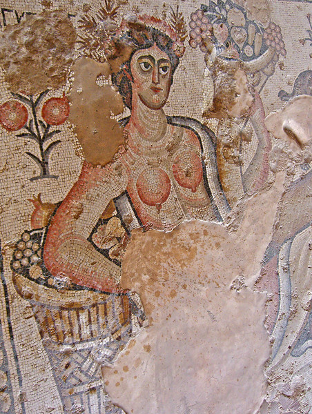 "6-In the upper left of the ""Nile"" mosaic, a reclining female—identified with Egypt in Greek letters—holds a cornucopia of fruit in one hand, the other arm rests on a basket of fruits."