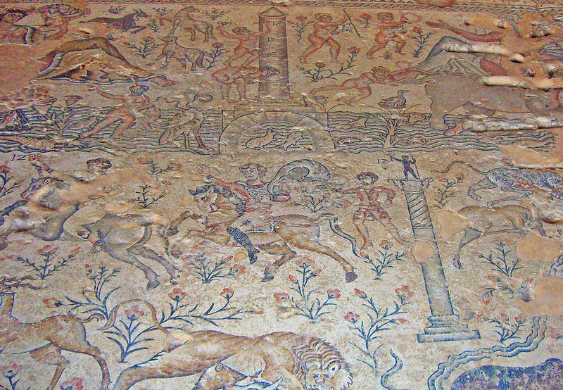 4-Mosaic floor (22 ft x 20 ft) recovered in a 5th century CE public building (ground floor area of 16,000 sq. ft.). Depicts celebrations for the rise of the Nile River water to its peak. Visible at top is a Nilometer, which measured the height of the water and determined the tax rate for that year. The man standing on the woman's shoulders is engraving the number IZ (17)—the height of the water (which runs across the panel below the Nilometer). Below the water, horsemen head to Alexandria with the good news. At lower right is the 3rd century CE Pompeii Column.