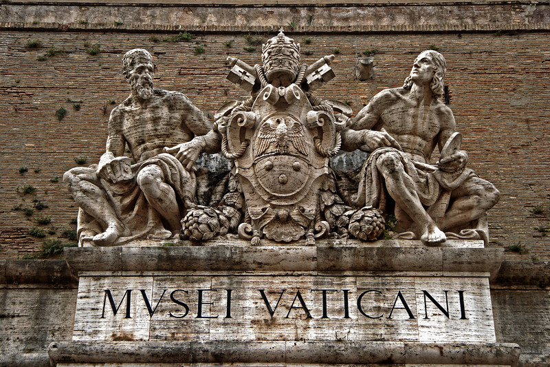 #0006 Vatican Museum Entrance<br /> The Statues above the entrance to the Vatican Museum were sculpted in 1932 by Pietro Melandri. Michelangelo is on the left and Raphael on the right with the Coat of Arms of Pius XI between them.