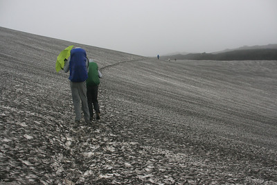 Shane offers the use of an umbrella to Jayna while crossing snow after leaving Landmannalaugar.