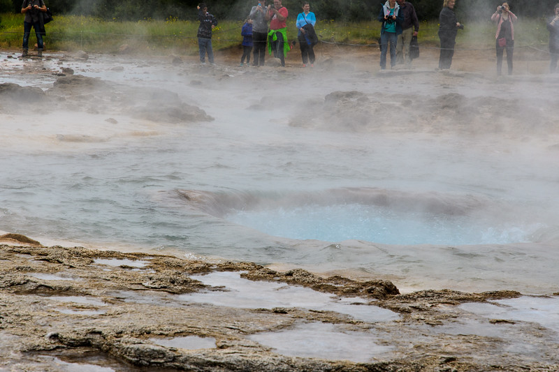 Strokkur geyser.  After the single burst, the water drains down the hill or back into the hole, where it is several inches below the surrounding surface until the next activity begins.