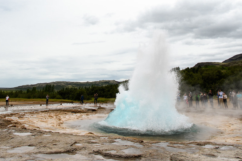 Strokkur geyser.  Suddenly a pyramid shaped column of hot water shoots up.