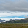 Blue sky just above the Skalafellsjokull glacier and below the bank of clouds.   Farms dot the area beneath the exposed mountains.
