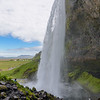 Seljalandsfoss pours over the cliff above onto the plain below allowing space behind where spectators can walk the slippery path behind.