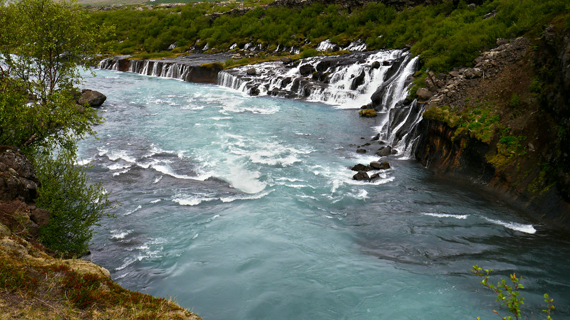 Iceland, June 2014, Overseas Adventure Travel (OAT) trip.<br /> Hraunfossar and Barnafoss waterfalls.  Hraunfossar (Borgarfjörður, western Iceland) is a series of waterfalls formed by rivulets streaming over a distance of about 900 metres out of the Hallmundarhraun, a lava field which flowed from an eruption of one of the volcanoes lying under the glacier Langjökull. The waterfalls pour into the Hvítá river from ledges of less porous rock in the lava. The name hraun comes from the Icelandic word for lava. The Hraunfossar are situated near Húsafell and Reykholt. Literally a stone's throw upstream from Hraunfossar, there is another waterfall called Barnafoss. Its name, the waterfall of the children, comes from an accident which is said to have taken place here in former times. There was a natural bridge over the waterfall and two children from a nearby farm fell to their deaths crossing the river on the bridge. Afterwards, the grief-struck mother had the bridge destroyed.