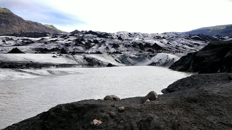 Iceland, June 2014, Overseas Adventure Travel (OAT) trip.  <br /> Solheimajokull Glacier.  It has retreated and melted quite a bit and this portion is covered with a lot of black ash. We could see some blue ice and water flowing in the crevices.