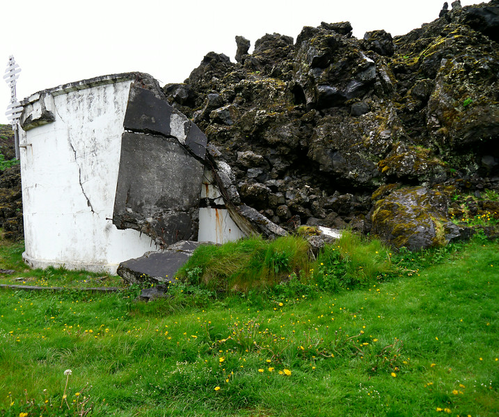 Iceland (Westman Island), June 2014, Overseas Adventure Travel (OAT) trip.<br /> A water tank partially consumed by the lava flow from the eruption in 1973.