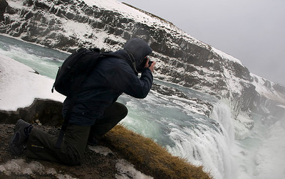 "Gullfoss (Golden Falls) is a massive waterfall located in the canyon of Hvítá river in southwest Iceland.  It is is one of the most popular tourist attractions in the country. The wide Hvítá rushes southward and 1km above the falls it turns sharply to the left and flows down into a wide curved three-step ""staircase"" and then abruptly plunges in two stages into a crevice 105 ft deep. The crevice is 60 ft wide, and 2.5 km in length, is at right angles to the flow of the river.   The part frozen falls took my breath away as I first approached. Spectacular is just not grand enough to describe it. I trust the pictures help. Me getting very close to the edge! Olympus E510 in action. Olympus E510, 14-42mm."