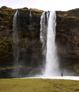 Seljalandsfoss is one of the most famous waterfalls of Iceland. It is very picturesque and situated between Selfoss and Skógafoss.This waterfall of the river Seljalandsá drops 60 metres (200 ft) over the cliffs of the former coastline.   It is possible to walk behind the waterfall albeit via a dodgy  icy, narrow track. Well worth it though as the view close up is breathtaking. Person added for scale :) Olympus E3 12-60mm.