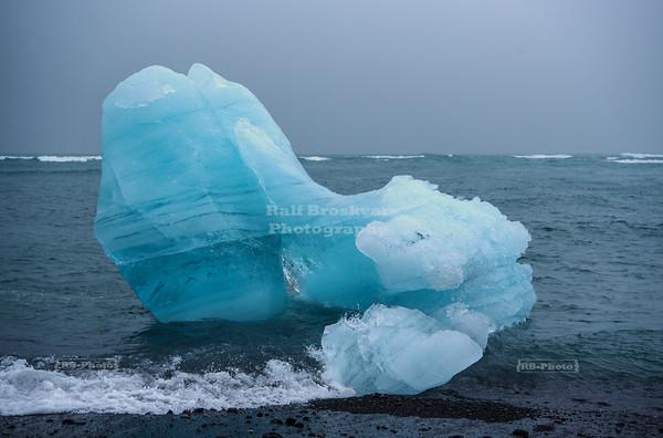 Blue Iceberg at the Black Breiðamerkursandur Beach in Southern Iceland