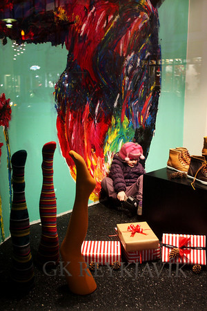 A little girl trying on heels in store window while parents were busy shopping.