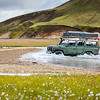 4WD car wades river in Landmannalaugar in Iceland
