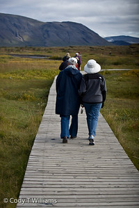 A couple walk tour Thingvellir National Park, a UNESCO's World Heritage site. One can observe the the geological wonder of the mid-Atlantic ridge, the drifting apart of the continental plate of Europe and North America in Iceland. September, 2009 © Cody T Williams.