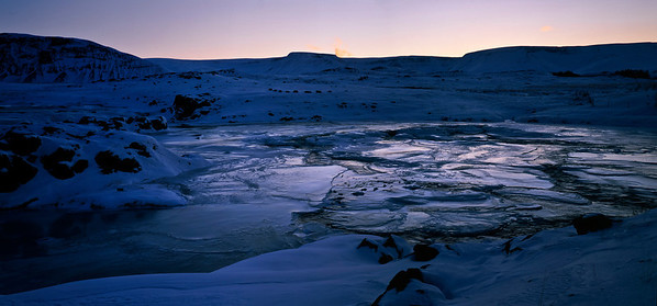 Flowing water forms thousands of terraces of ice, in the golden light of a December morning. Near Borgarnes, Iceland.