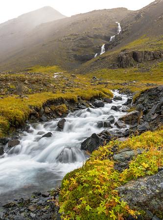 Waterfall in valley near cave waterfall Skútafoss