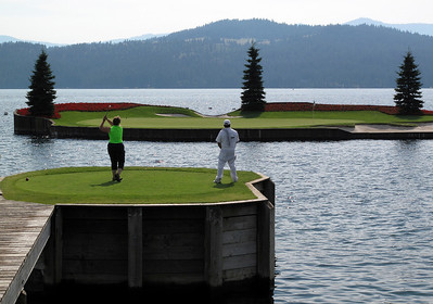A golfer and her forecaddie watch her shot fly onto the 14th green at The Coeur D'Alene Resort Golf Course.