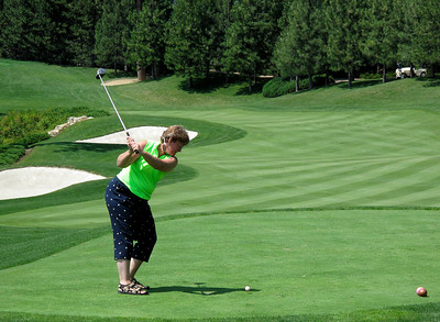 A golfer drives her ball down the fourth fairway of The Coeur D'Alene Resort Golf Course.