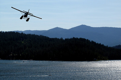 An airplane approches Lake Coeur D'Alene to make a landing on the water.
