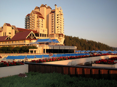 The Coeur D'Alene Resort hotel stands in the sunlight of a summer evening.