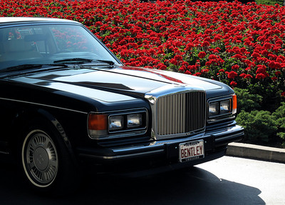 A classic motorcar sits beside a bed of geraniums outside the Coeur D'Alene Resort hotel.