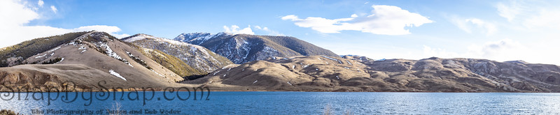 A panorama of snow covered mountains with a lake and blue skies with some white clouds