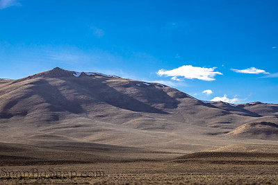 A mountain standing in front of a rugged prairie with brilliant blue skies with clouds