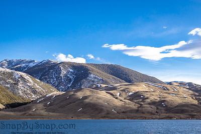A snow covered mountain with a lake and blue skies with some white clouds