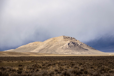 A small bright mountain contrasting against a darker colored prairie with storm clouds behind it