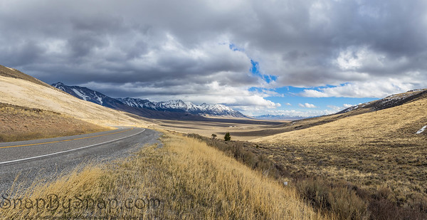 A road curving to the left and revealing an epic mountain and prairie landscape with snow covered peaks