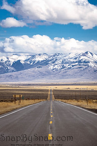 A long, straight road heading into the distant mountains