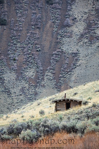 An old settler's cabin sitting on the side of a mountain in Idaho