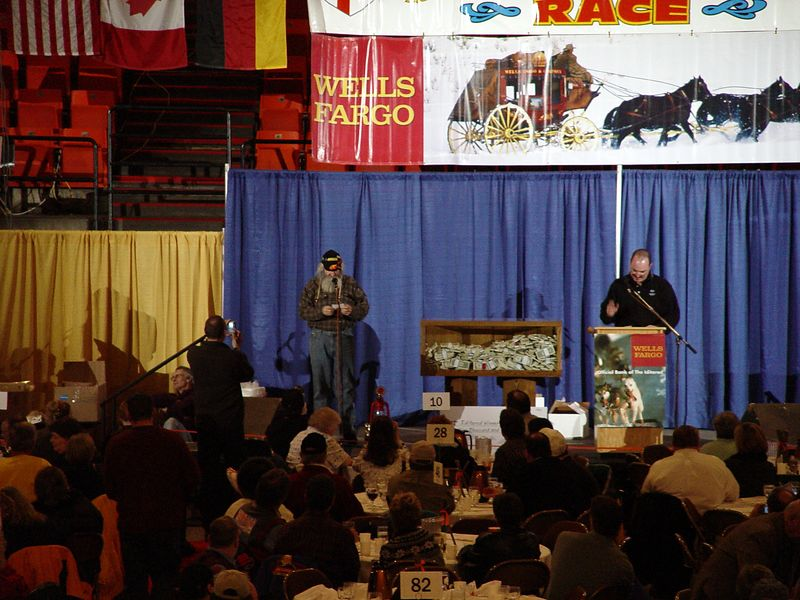 """Musher Charlie Boulding (finished sixth) getting his bib number at the mushers' banquet in Anchorage.  One rookie who got his number late in the evening said """"They told me the Iditarod was tough, but it can't be as tough as sitting through this banquet.""""  It lasted from 6:00 until 11:00!"""