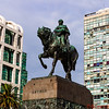 Bronze statue of Uruguay's National hero Jose Gervasio Artigas.   The statue is located above his mausoleum on Independence Square.  The buildings in the back reflect a range of styles.