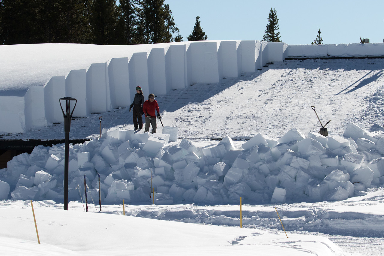 After stopping at a Warming Hut nearby, we saw this strange sight at a distance and went to investigate,.  These workers are clearing the enormous snow load off this building by cutting multi-hundred  pound cubes of snow and moving them off the edge.