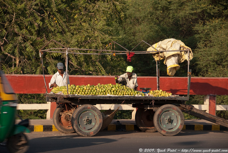 A vendor sells fruit at the side of a busy road.