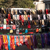 A colorful display of hats and scarves by a street vendor.