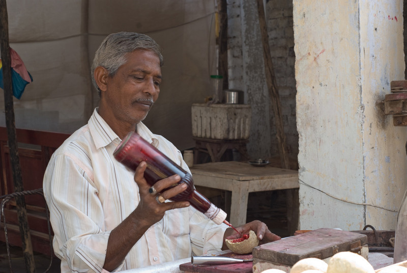 Preparing the wood apple for eating. The fruit itself is really sour, so he adds sugar and spices and some rose syrup.