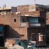 "Some construction in India amazes me. These are ""low income"" multi-story residences, built by hand with bricks individually accumulated over time. No building inspector has or will go through here. I'm not sure of the structural integrity of this place, but people certainly live there!"