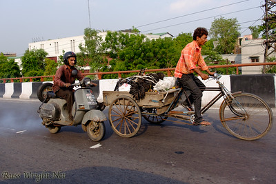 Hard enough cycling with a heavy load to have a smoke belching scooter come by. New Delhi, India. 2015