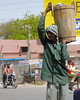 A man carries a barrel of food.