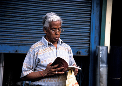 Reading book on the street, Kolkata.