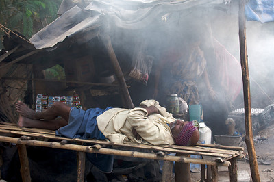 Man having afternoon nap while his wife burns the food and heavy traffic is passing by along a busy main road. Kolkata.