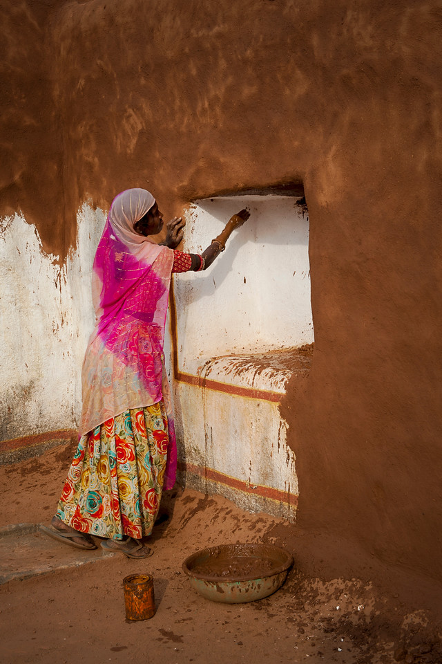 Applying a mixture of mud and dung to a village home