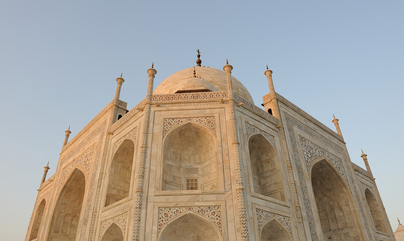 "The Taj Mahal was built on a parcel of land to the south of the walled city of Agra. Shah Jahan presented Maharajah Jai Singh with a large palace in the center of Agra in exchange for the land.[18] An area of roughly three acres was excavated, filled with dirt to reduce seepage and leveled at 50 meters above riverbank. In the tomb area, wells were dug and filled with stone and rubble as the footings of the tomb. Instead of lashed bamboo, workmen constructed a colossal brick scaffold that mirrored the tomb. The scaffold was so enormous that foremen estimated it would take years to dismantle. According to the legend, Shah Jahan decreed that anyone could keep the bricks taken from the scaffold, and thus it was dismantled by peasants overnight. A fifteen kilometer tamped-earth ramp was built to transport marble and materials to the construction site. Teams of twenty or thirty oxen were strained to pull blocks on specially constructed wagons. An elaborate post-and-beam pulley system was used to raise the blocks into desired position. Water was drawn from the river by a series of purs, an animal-powered rope and bucket mechanism, into a large storage tank and raised to large distribution tank. It was passed into three subsidiary tanks, from which it was piped to the complex.<br /> The plinth and tomb took roughly 12 years to complete. The remaining parts of the complex took an additional 10 years and were completed in order of minarets, mosque and jawab and gateway. Since the complex was built in stages, discrepancies exist in completion dates due to differing opinions on ""completion"". For example, the mausoleum itself was essentially complete by 1643, but work continued on the rest of the complex. Estimates of the cost of the construction of Taj Mahal vary due to difficulties in estimating construction costs across time. The total cost of construction has been estimated to be about 32 million Rupees at that time which now runs into trillions of Dollars if converted to present currency rates.[19]<br /> The Taj Mahal was constructed using materials from all over India and Asia. Over 1,000 elephants were used to transport building materials during the construction. The translucent white marble was brought from Rajasthan, the jasper from Punjab, jade and crystal from China. The turquoise was from Tibet and the Lapis lazuli from Afghanistan, while the sapphire came from Sri Lanka and the carnelian from Arabia. In all, twenty eight types of precious and semi-precious stones were inlaid into the white marble.<br /> <br /> <br /> Artist's impression of the Taj Mahal, from the Smithsonian Institution<br /> A labour force of twenty thousand workers was recruited across northern India. Sculptors from Bukhara, calligraphers from Syria and Persia, inlayers from southern India, stonecutters from Baluchistan, a specialist in building turrets, another who carved only marble flowers were part of the thirty-seven men who formed the creative unit. Some of the builders involved in construction of Taj Mahal are:<br /> The main dome was designed by Ismail Afandi (a.ka. Ismail Khan),[20] of the Ottoman Empire and was considered as a premier designer of hemispheres and domes.<br /> Ustad Isa of Persia (Iran) and Isa Muhammad Effendi of Persia (Iran), trained by Koca Mimar Sinan Agha of Ottoman Empire, are frequently credited with a key role in the architectural design,[21][22] but there is little evidence to support this claim.<br /> 'Puru' from Benarus, Persia (Iran) has been mentioned as a supervising architect.[23]<br /> Qazim Khan, a native of Lahore, cast the solid gold finial.<br /> Chiranjilal, a lapidary from Delhi, was chosen as the chief sculptor and mosaicist.<br /> Amanat Khan from Shiraz, Iran was the chief calligrapher. His name has been inscribed at the end of the inscription on the Taj Mahal gateway.[24]<br /> Muhammad Hanif was a supervisor of masons and Mir Abdul Karim and Mukkarimat Khan of Shiraz, Iran (Persia) handled finances and management of daily production."