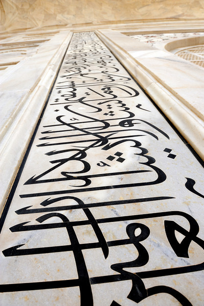 "As one enters through Taj Mahal Gate, the calligraphy reads ""O Soul, thou art at rest. Return to the Lord at peace with Him, and He at peace with you.""[11][10]<br /> Abstract forms are used especially in the plinth, minarets, gateway, mosque, jawab, and to a lesser extent, on the surfaces of the tomb. The domes and vaults of sandstone buildings are worked with tracery of incised painting to create elaborate geometric forms. On most joining areas, herringbone inlays define the space between adjoining elements. White inlays are used in sandstone buildings and dark or black inlays on the white marbles. Mortared areas of marble buildings have been stained or painted dark and thus creating a geometric patterns of considerable complexity. Floors and walkways use contrasting tiles or blocks in tessellation patterns.<br /> Vegetative motifs are found at the lower walls of the tomb. They are white marble dados that have been sculpted with realistic bas relief depictions of flowers and vines. The marble has been polished to emphasise the exquisite detailing of these carvings. The dado frames and archway spandrels have been decorated with pietra dura inlays of highly stylised, almost geometric vines, flowers and fruits. The inlay stones are yellow marble, jasper and jade, leveled and polished to the surface of the walls."