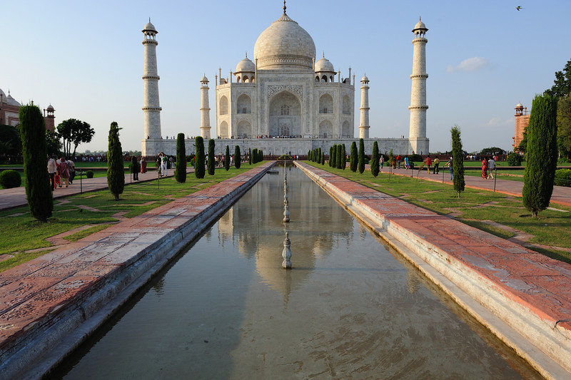 """The complex is set around a large 300-meter square charbagh, a Mughal garden. The garden uses raised pathways that divide each of the four quarters of the garden into 16 sunken parterres or flowerbeds. A raised marble water tank at the center of the garden, halfway between the tomb and gateway, with a reflecting pool on North-South axis reflects the image of the Taj Mahal. Elsewhere, the garden is laid out with avenues of trees and fountains.[12] The raised marble water tank is called al Hawd al-Kawthar, in reference to """"Tank of Abundance"""" promised to Muhammad.[13] The charbagh garden, a design inspired by Persian gardens, was introduced to India by the first Mughal emperor Babur. It symbolizes four flowing rivers of Paradise and reflects the gardens of Paradise derived from the Persian paridaeza, meaning 'walled garden'. In mystic Islamic texts of Mughal period, paradise is described as an ideal garden of abundance with four rivers flowing from a central spring or mountain, separating the garden into north, west, south and east.<br /> <br /> <br /> Walkways beside reflecting pool<br /> Most Mughal charbaghs are rectangular with a tomb or pavilion in the center. The Taj Mahal garden is unusual in that the main element, the tomb, instead is located at the end of the garden. With the discovery of Mahtab Bagh or """"Moonlight Garden"""" on the other side of the Yamuna, Archaeological Survey of India interprets that the Yamuna itself was incorporated into the garden's design and was meant to be seen as one of the rivers of Paradise.[14] The similarity in layout of the garden and its architectural features such as fountains, brick and marble walkways, and geometric brick-lined flowerbeds with Shalimar's suggest that the garden may have been designed by the same engineer, Ali Mardan.[15] Early accounts of the garden describe its profusion of vegetation, including roses, daffodils, and fruit trees in abundance.[16] As the Mughal Empire declined, the tending of the garden decline"""