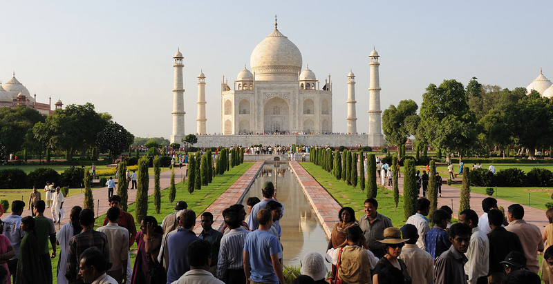 "The focus of the Taj Mahal is the white marble tomb, which stands on a square plinth consisting of a symmetrical building with an iwan, an arch-shaped doorway, topped by a large dome. Like most Mughal tombs, basic elements are Persian in origin.<br /> <br /> <br /> The base structure is a large, multi-chambered structure. The base is essentially a cube with chamfered edges and is roughly 55 meters on each side (see floor plan, right). On the long sides, a massive pishtaq, or vaulted archway, frames the iwan with a similar arch-shaped balcony.<br /> On either side of the main arch, additional pishtaqs are stacked above and below. This motif of stacked pishtaqs is replicated on chamfered corner areas as well. The design is completely symmetrical on all sides of the building. Four minarets, one at each corner of the plinth, facing the chamfered corners, frame the tomb. The main chamber houses the false sarcophagi of Mumtaz Mahal and Shah Jahan; their actual graves are at a lower level.<br /> The marble dome that surmounts the tomb is its most spectacular feature. Its height is about the same size as the base of the building, about 35 meters, and is accentuated as it sits on a cylindrical ""drum"" of about 7 metres high. Because of its shape, the dome is often called an onion dome (also called an amrud or guava dome). The top is decorated with a lotus design, which serves to accentuate its height as well. The shape of the dome is emphasised by four smaller domed chattris (kiosks) placed at its corners. The chattri domes replicate the onion shape of the main dome. Their columned bases open through the roof of the tomb and provide light to the interior. Tall decorative spires (guldastas) extend from edges of base walls, and provide visual emphasis to the height of the dome. The lotus motif is repeated on both the chattris and guldastas. The dome and chattris are topped by a gilded finial, which mixes traditional Persian and Hindu decorative elements.<br /> The main dome is crowned by a gilded spire or finial. The finial, made of gold until the early 1800s, is now made of bronze. The finial provides a clear example of integration of traditional Persian and Hindu decorative elements. The finial is topped by a moon, a typical Islamic motif, whose horns point heavenward. Because of its placement on the main spire, the horns of moon and finial point combine to create a trident shape, reminiscent of traditional Hindu symbols of Shiva.[8]<br /> At the corners of the plinth stand minarets, the four large towers each more than 40 meters tall. The minarets display the Taj Mahal's penchant for symmetry. These towers are designed as working minarets, a traditional element of mosques as a place for a muezzin to call the Islamic faithful to prayer. Each minaret is effectively divided into three equal parts by two working balconies that ring the tower. At the top of the tower is a final balcony surmounted by a chattri that mirrors the design of those on the tomb. The minaret chattris share the same finishing touches, a lotus design topped by a gilded finial. Each of the minarets were constructed slightly outside of the plinth, so that in the event of collapse, a typical occurrence with many such tall constructions of the period, the material from the towers would tend to fall away from the tomb."